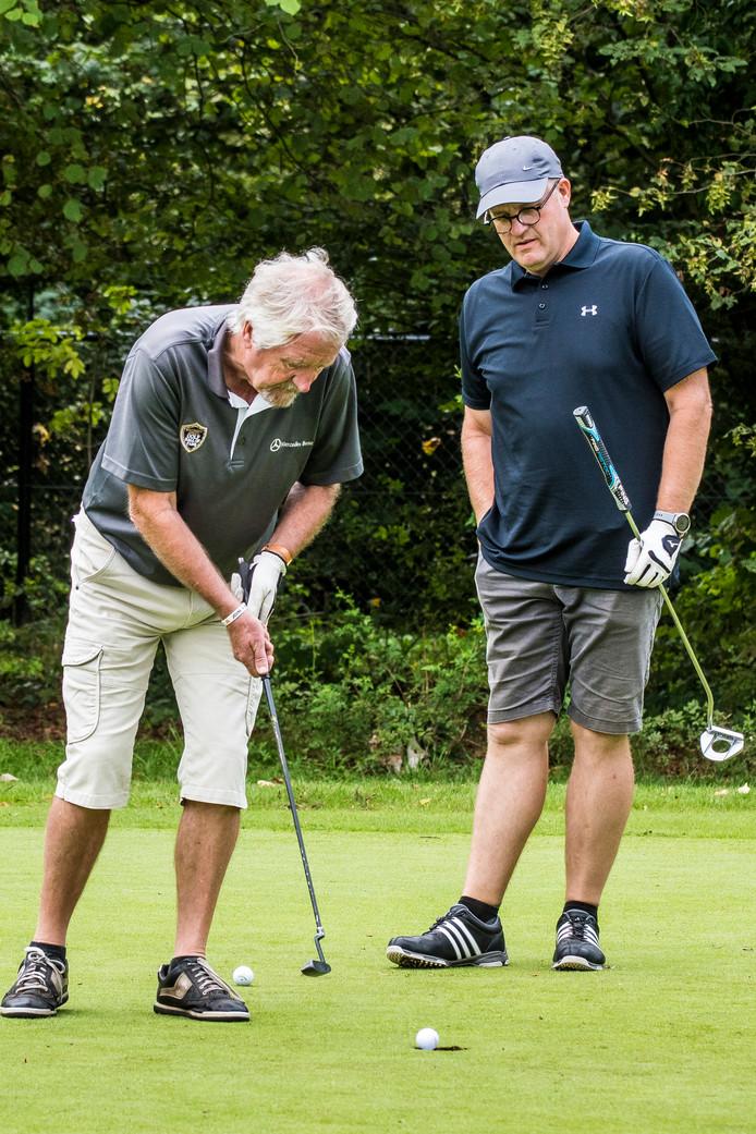 Een man, een club, een bal en een put. Golfen.
