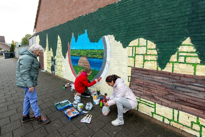 Streetartpainter Maureen Kolhoff (m) beschildert de blinde muur van de woning van Beppy van Rossum (r) in De Laar-Oost in Arnhem. Met overbuurvrouw Tiny Sijbrandi (l) nam Van Rossum het initiatief voor de muurschildering.