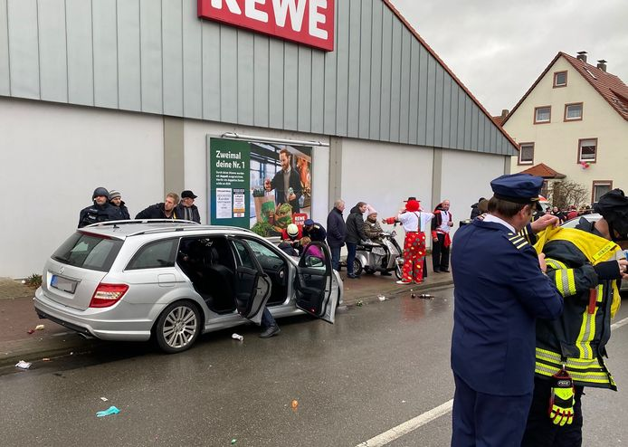 Policemen stand next to a car in front of a supermarket in Volkmarsen near Kassel, central Germany, on Rose Monday, February 24, 2020. - Several people were injured when a car drove into a carnival procession in Volksmarsen, police said, adding that the driver had been arrested. (Photo by Elmar SCHULTEN / AFP)