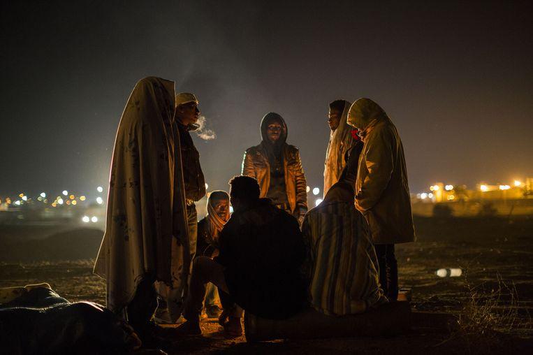 Afrikaanse asielzoekers verzamelen zich rond een vuur voor het Holot detentiecentrum. Beeld getty
