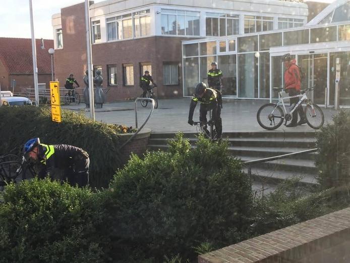 De oefenende agenten nemen op hun mountainbikes de trap voor het gemeentehuis in Elst.
