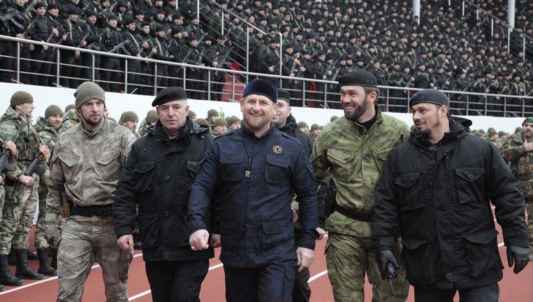 President Kadyrov (midden) paradeert tussen zijn hoogste commandanten in het stadion van Grozny in december 2014 voor 20.000 militieleden. Beeld AP