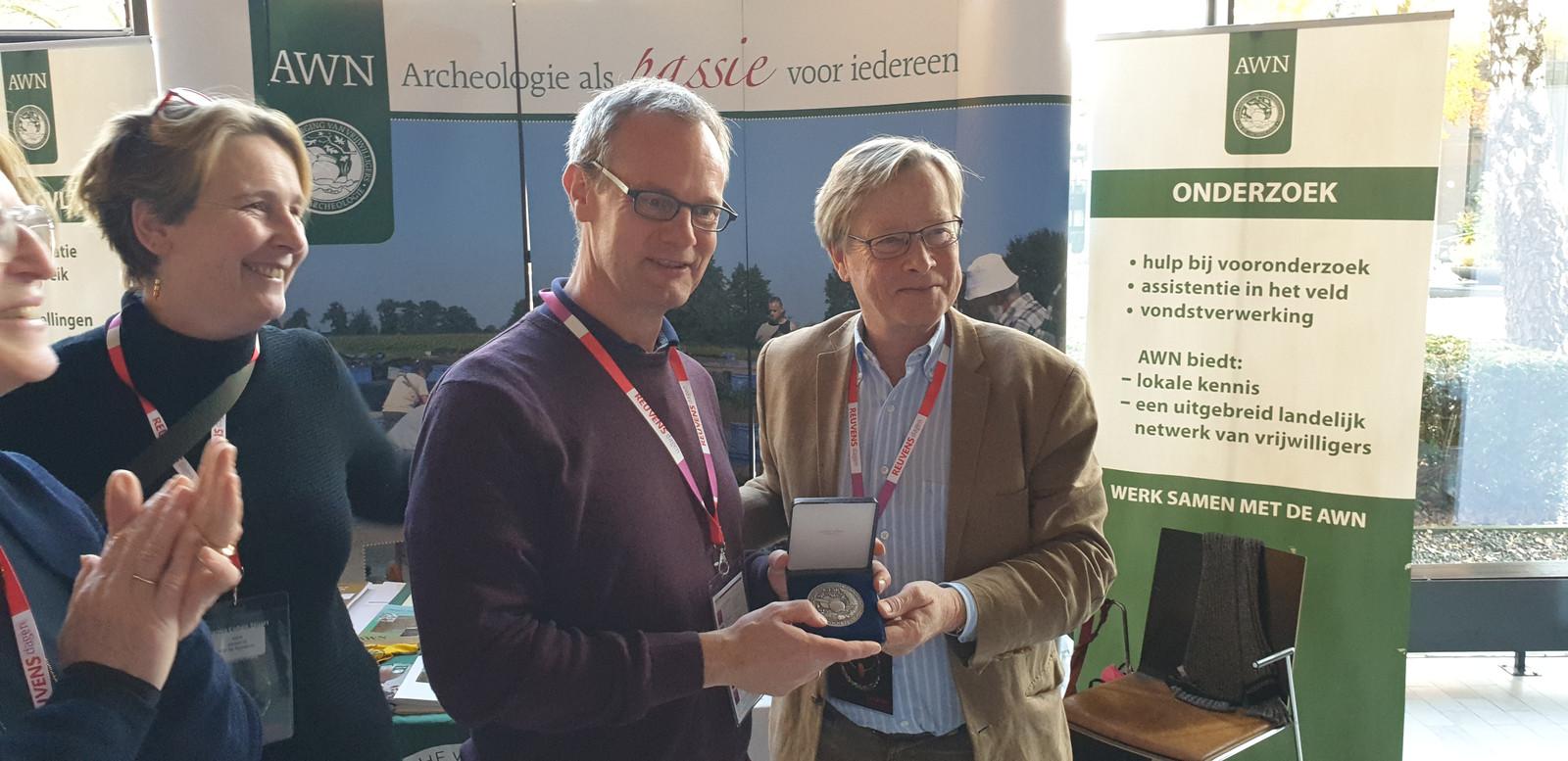 Voorzitter Gajus Scheltema (rechts) van de AWN heeft de legpenning overhandigd aan de Zutphense stadsarcheoloog Michel Groothedde.