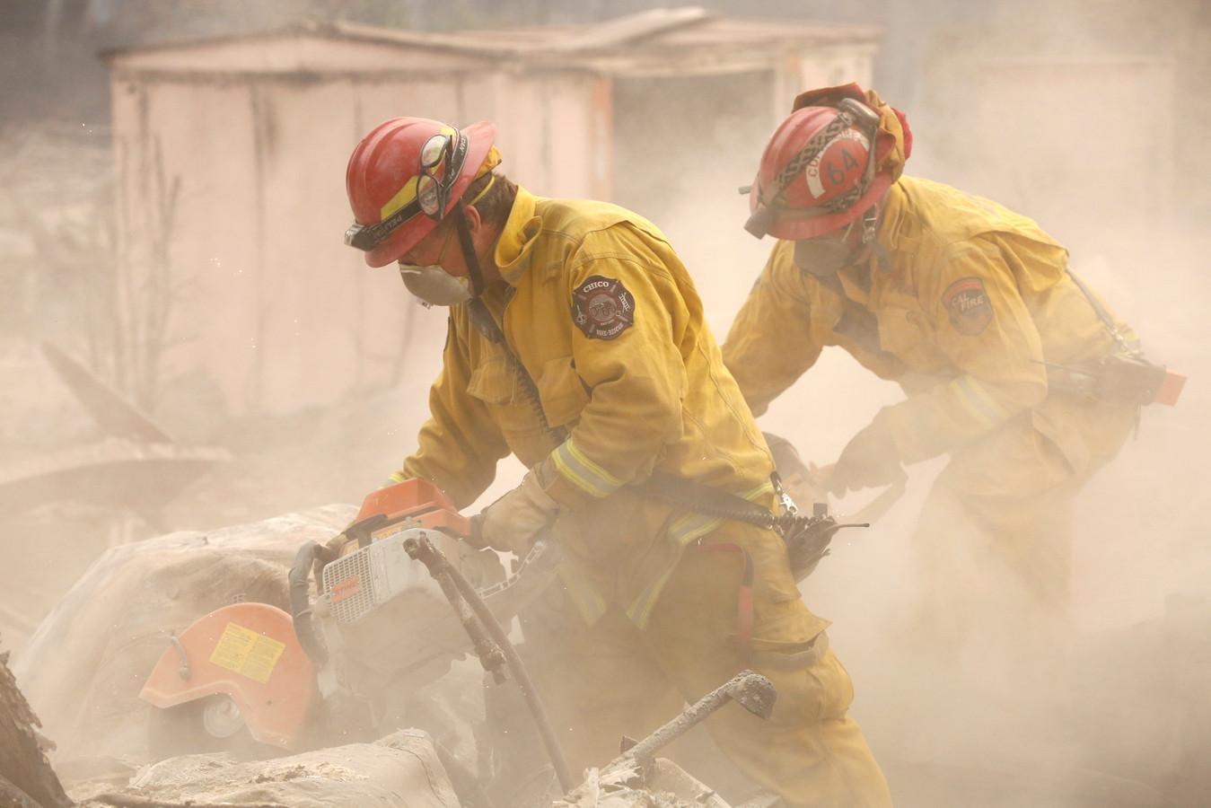 Brandweerlieden doorzoeken een huis dat in as is gelegd door Camp Fire.