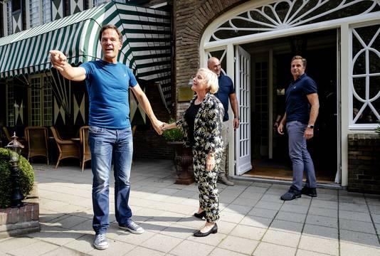 Minister Ank Bijleveld (Defensie) maant premier Mark Rutte weer mee naar binnen te gaan.