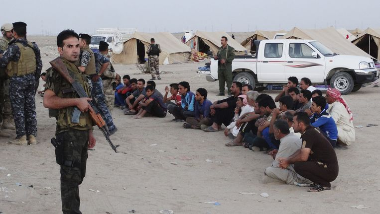 Iraakse vluchtelingen bij een controlepost op IS-strijders in een kamp ten westen van Bagdad.