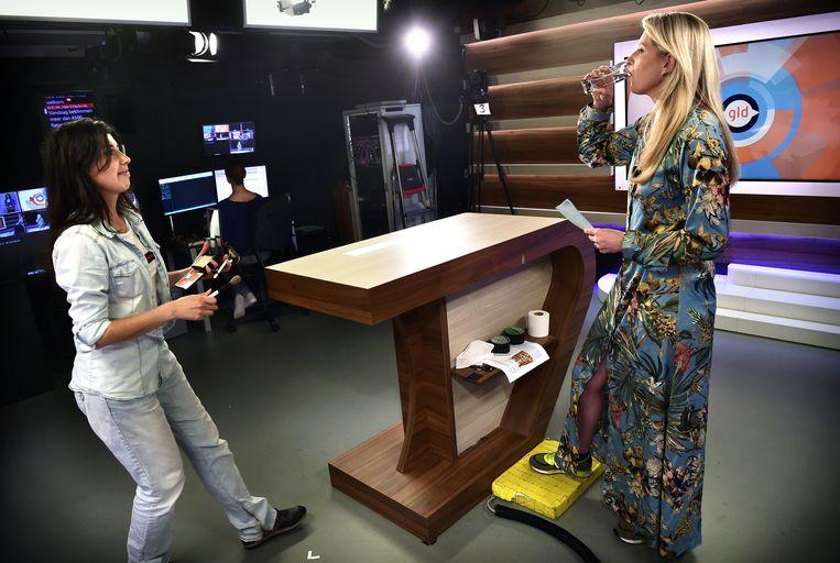 De presentatrice van een nieuwsuitzending bij Omroep Gelderland neemt vlak voor de uitzending nog een slok water.  Beeld Marcel van den Bergh / de Volkskrant