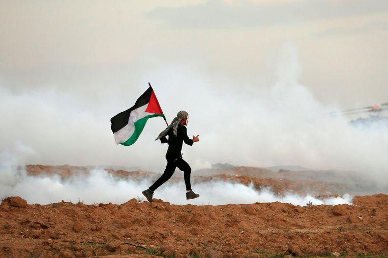 Een Palestijn rent met een Palestijnse vlag in zijn handen, tijdens een zoveelste protestactie vlakbij de grens met Israël.(Photo by MAHMUD HAMS / AFP)