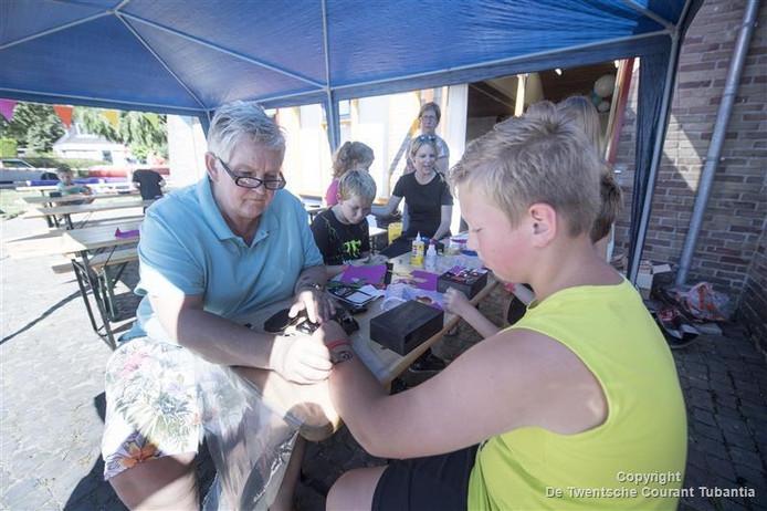 Kinderen uit Westerhaar genieten van de Jeugd Vakantiespelen. Metje Schutte is één van de begeleidster. Hier plakt ze een tattoo bij één van de kinderen.