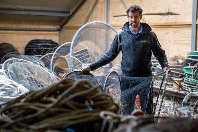 Visser Stefan Lok is druk in de weer om zijn vissersnetten te repareren.