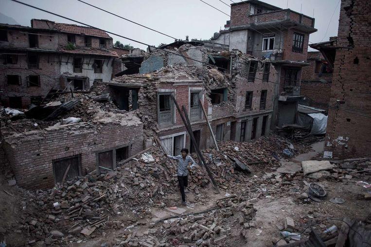 Een Nepalees loopt langs verwoeste gebouwen in een voorstad van Kathmandu. Beeld afp