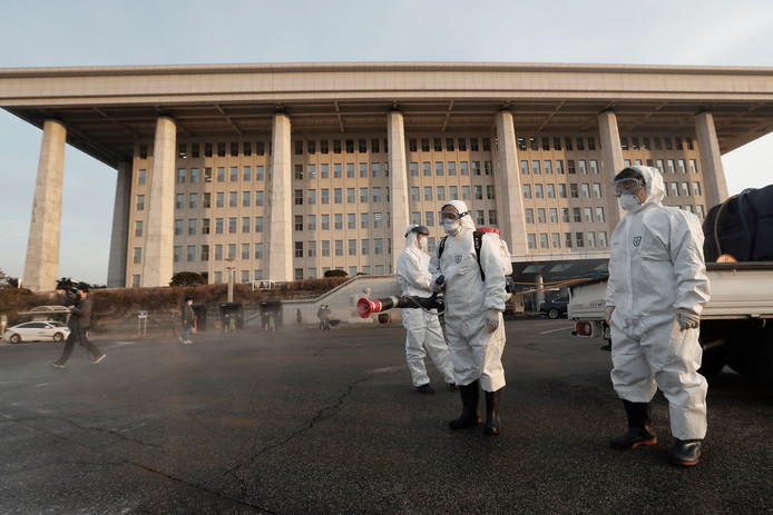 Werkers sproeien desinfecterende spray in Zuid-Korea.
