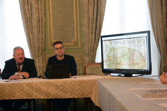 Projectcoördinator Hans De Bock en burgemeester Van de Vijver tonen enkele archiefstukken die voortaan digitaal te raadplegen zijn.