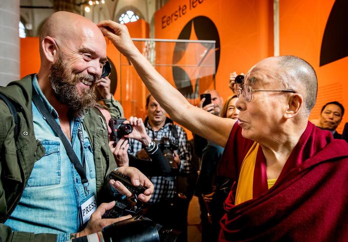 De Dalai Lama voelt even aan het hoofd van de fotograaf
