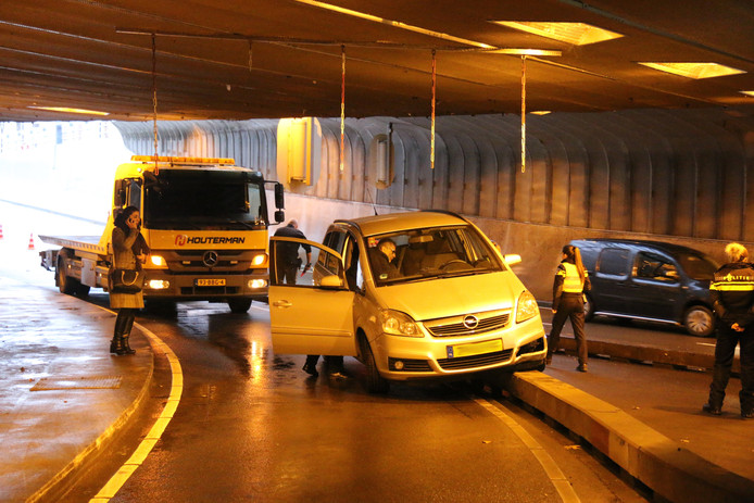 Auto rijdt tegen betonnen wegafscheiding in de Willemstunnel.
