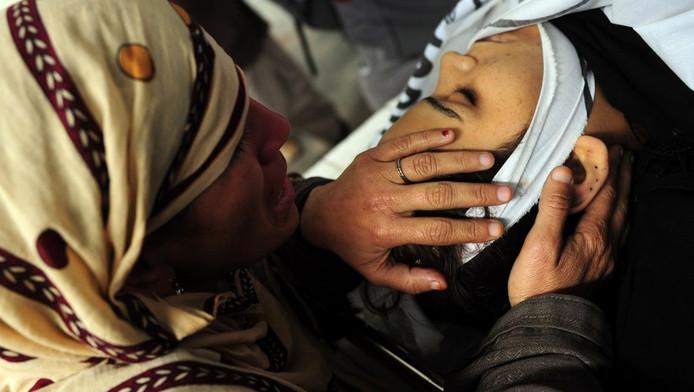 Een moeder huilt bij het lichaam van haar dochter, een van de hulpverleensters die in Karachi is vermoord.