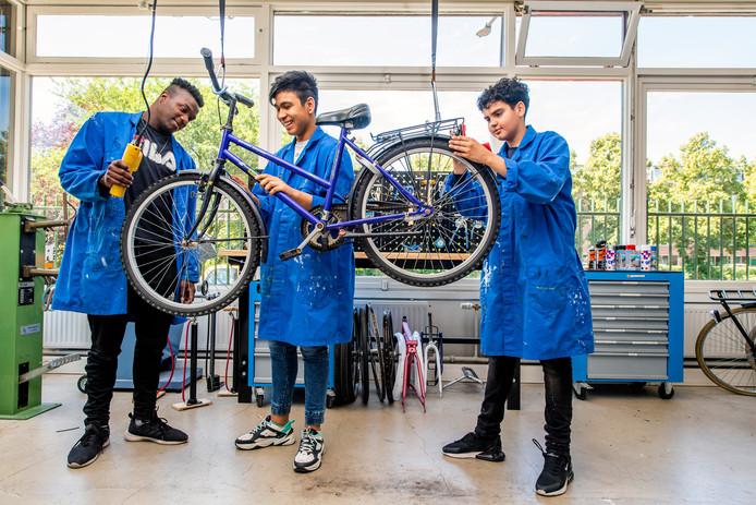 Theeshone Clarinda, Hassan Redzeb en Hamza Kassmi in de fietsenwerkplaats van Het Praktijkcollege Charlois.