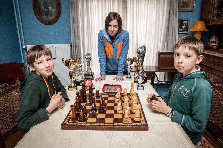 Igor (10, links) en broer Ilja (11) aan het schaakbord. Zus Daria (12) kijkt toe. Igor en Daria mogen in het najaar naar het wereldkampioenschap.
