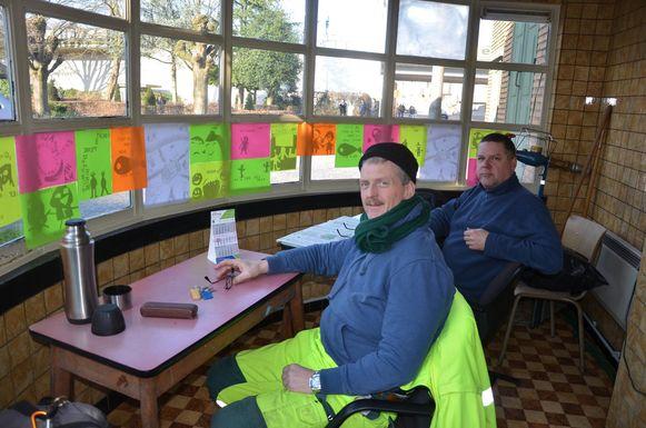 Serge Cousens en Geert Smet van de stedelijke reinigingsdienst kunnen de kunstwerkjes in het tramhuisje wel appreciëren.