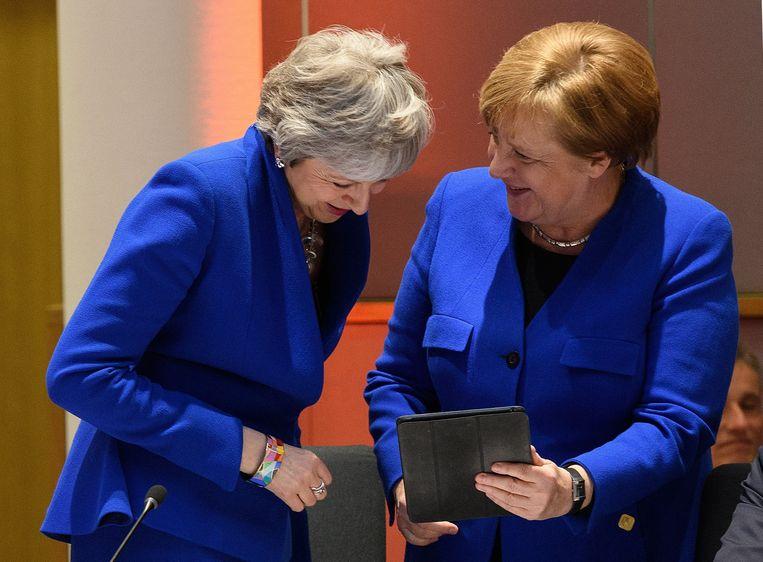 De Britse premier Theresa May (links) en de Duitse bondskanselier Angela Merkel vermaken zich in Brussel om foto's die Merkel op haar tablet toont van eerder op de dag, in hun eigen parlementen, toen de twee ook al dezelfde kleur droegen.  Beeld Photo News