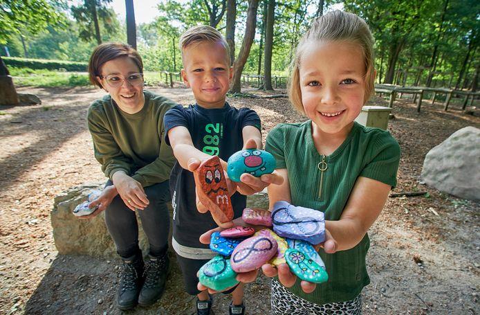 Loes Loocks Raaijmakers  en haar kinderen Rens en Fleur die zelfbeschilderde stenen in het bos neerleggen  zodat andere mensen ze vinden. Gisteren hebben ze de stenen op de foto in Herperduin neergelegd.