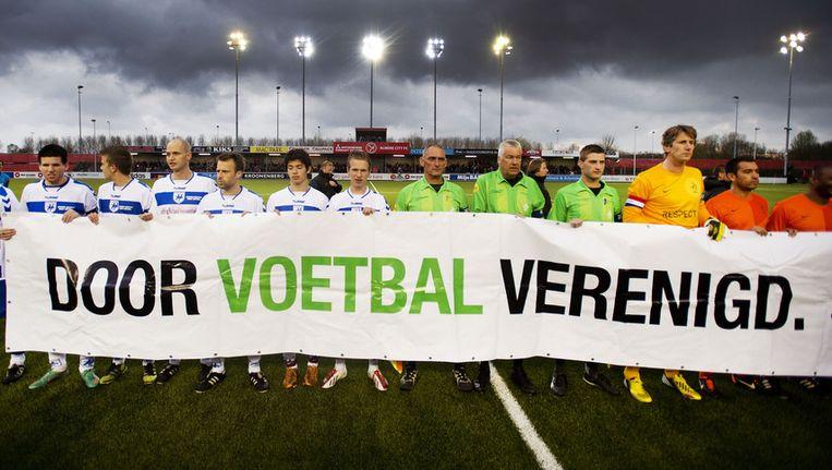 De teams van SC Buitenboys en Ex-internationals met de scheidsrechters voor de benefietwedstrijd na de dood van grensrechter Richard Nieuwenhuizen Beeld anp