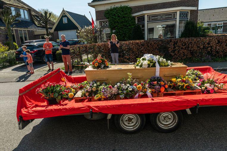Fotograaf Henk de Weerd (67) stierf aan corona. Bij zijn begrafenis klappen dorpsgenoten en geliefden en nemen afscheid, in Berkhout.  Beeld BSR Agency