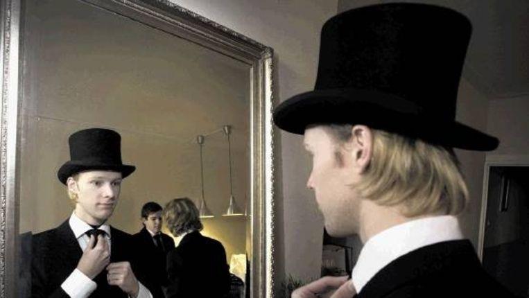 Eén voor een gaan de dragers voor de spiegel het gevecht met de stropdas aan. Fris en glad geschoren. (LAURENS AAIJ) Beeld