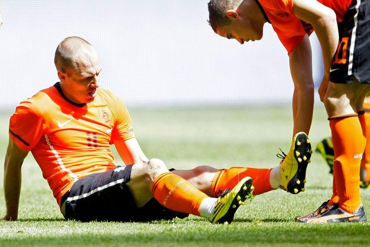 Ibrahim Afellay schudt het been van Arjan Robben die last heeft van een hamstringblessure. Beeld ap