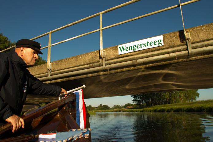 Een schipper stuurt een Berkelzomp onder een lage brug door op de Berkel bij Lochem.