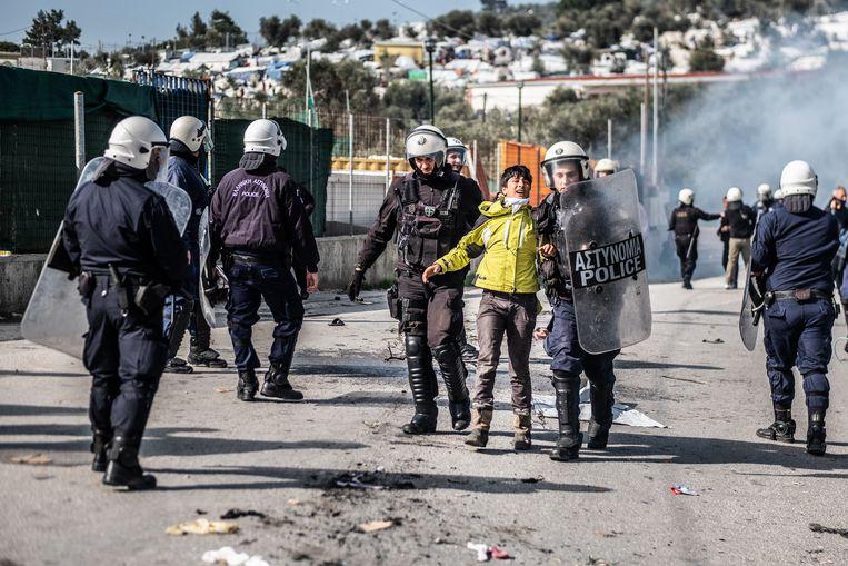 Enkele honderden migranten zijn maandag slaags geraakt met de Griekse politie toen ze wilden demonstreren tegen de leefomstandigheden in het beruchte kamp Moria. Beeld Joris Van Gennip