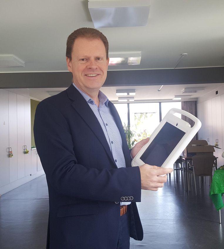 Voorzitter Tom Lacres met de nieuwe iPad in de hand.