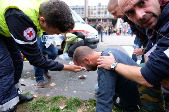 Een man die werd getroffen door traangas krijgt verzorging bij het Rode Kruis.
