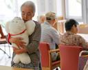 Een Japanse oudere knuffelt robotzeehondje Paro.