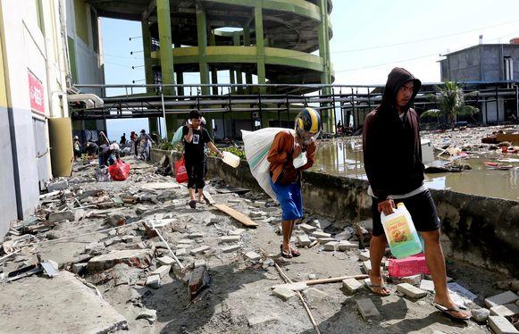 Plunderaars aan een vernield shoppingcenter in Palu.