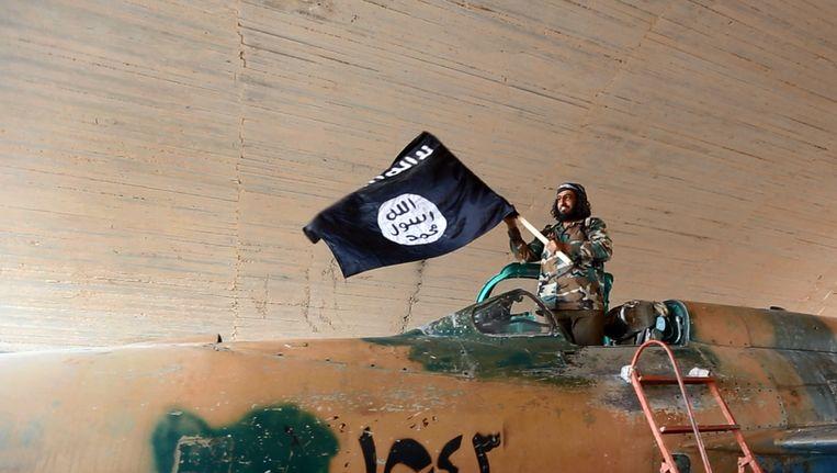 Een foto van een strijder van Islamitische Staat die zwaait met de vlag van de organisatie. Beeld AP