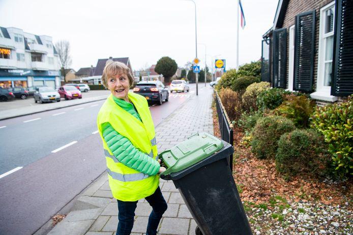 Ella Roelfs zet in december 2019 de vuilnis aan de weg; met een hesje aan om ongevallen te voorkomen. Op de achtergrond het zebrapad bij de Lidl.