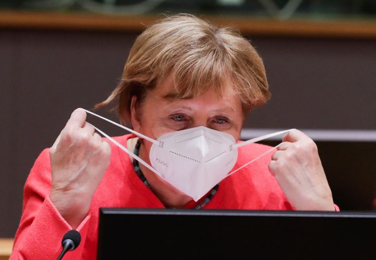 Angela Merkel doet een mondkapje voor. Beeld AP