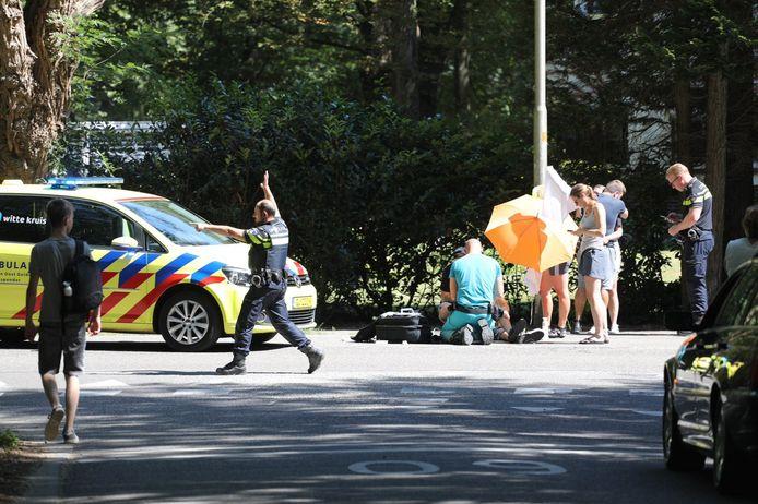 Een parasol en doeken houdt een gewonde fietser in de schaduw op de Loenenseweg in Beekbergen. De jongeman is zwaargewond naar het Gelre in Apeldoorn gebracht.