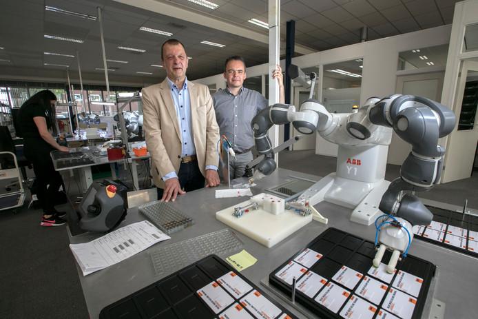 Rob van Berkom (l) en Mike Verjans bij een cobot op de assemblage-afdeling van Deonet.