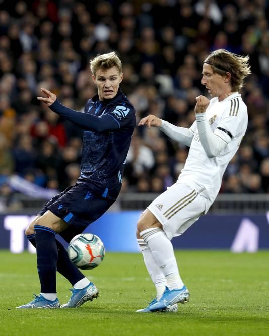 Martin Odegaard (links) in een gevecht om de bal met Luka Modric.