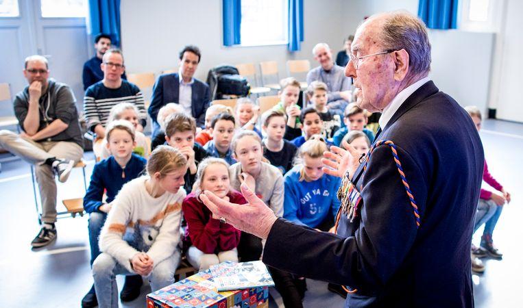 De 94-jarige Engelandvaarder Rudi Hemmes tussen de kinderen op de Schmidtschool in Den Haag. Hemmes overhandigde het eerste exemplaar van het Denkboek 2018. Beeld Freek van den Bergh / de Volkskrant
