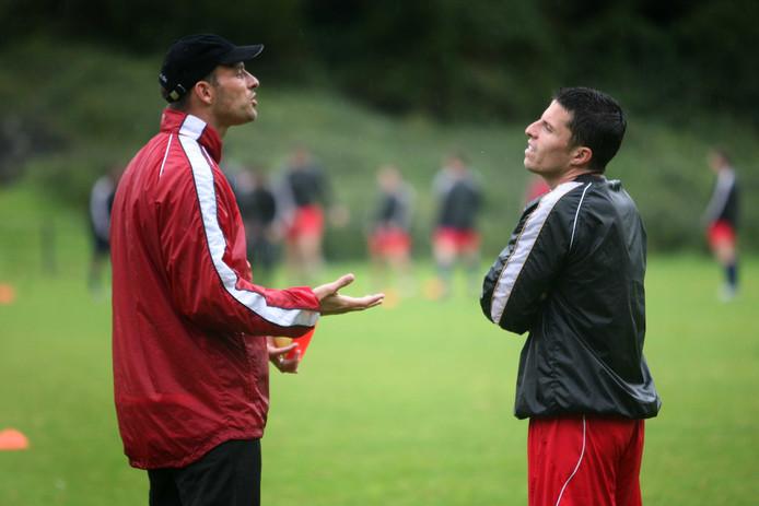 Arie van Lent, gewapend tegen de regen met regenjas en pet, als trainer van FC Kleve.