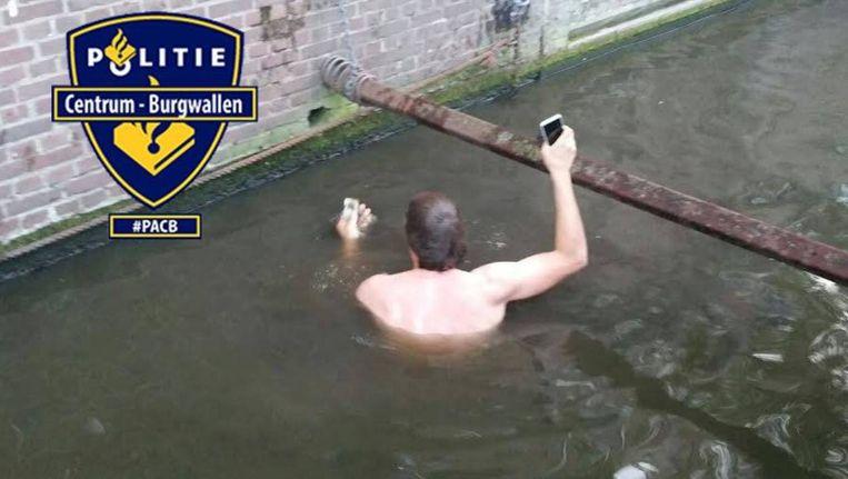 Politie Amsterdam Centrum-Burgwallen plaatste foto's van de zwemmende agent op Facebook. Beeld Facebook/Politie Amsterdam Centrum-Burgwallen