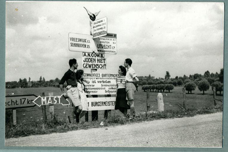 Twee Joodse stellen laten zich fotograferen voor een bewegwijzeringsbord van de ANWB. Beeld The Ghetto Fighters' House, Israël / The Photo Archive