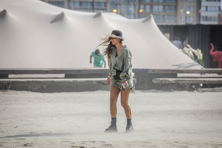Een bezoekster aan het festival WECANDANCE amuseert zich in het opstuivende zand.
