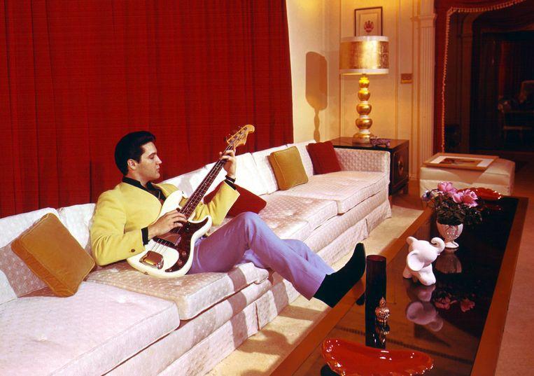 Elvis met zijn gitaar op de bank in Graceland. Beeld Charles Nicholas/Hollandse Hoogte