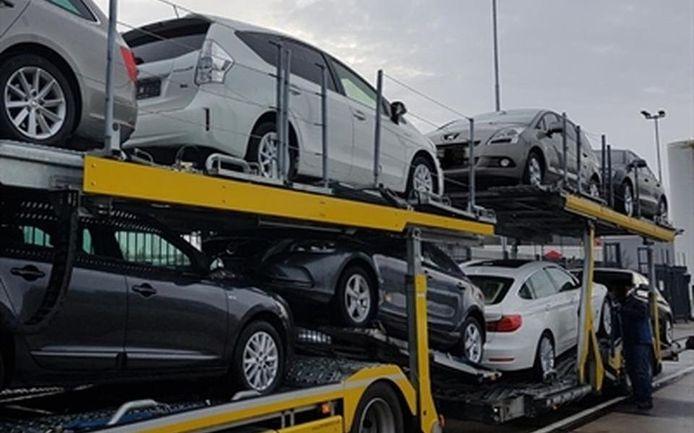 Bij een inval bij de Drentse autohandelaren in 2017 neemt de politie auto's in beslag.