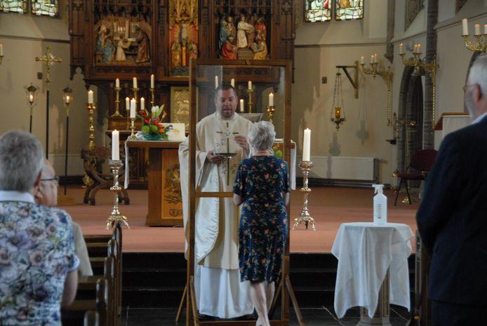Kapelaan Gideon van Meeteren deelt in de Lambertuskerk het Lichaam van Christus uit. Een transparant spatscherm scheidt de geestelijke van de communicanten.
