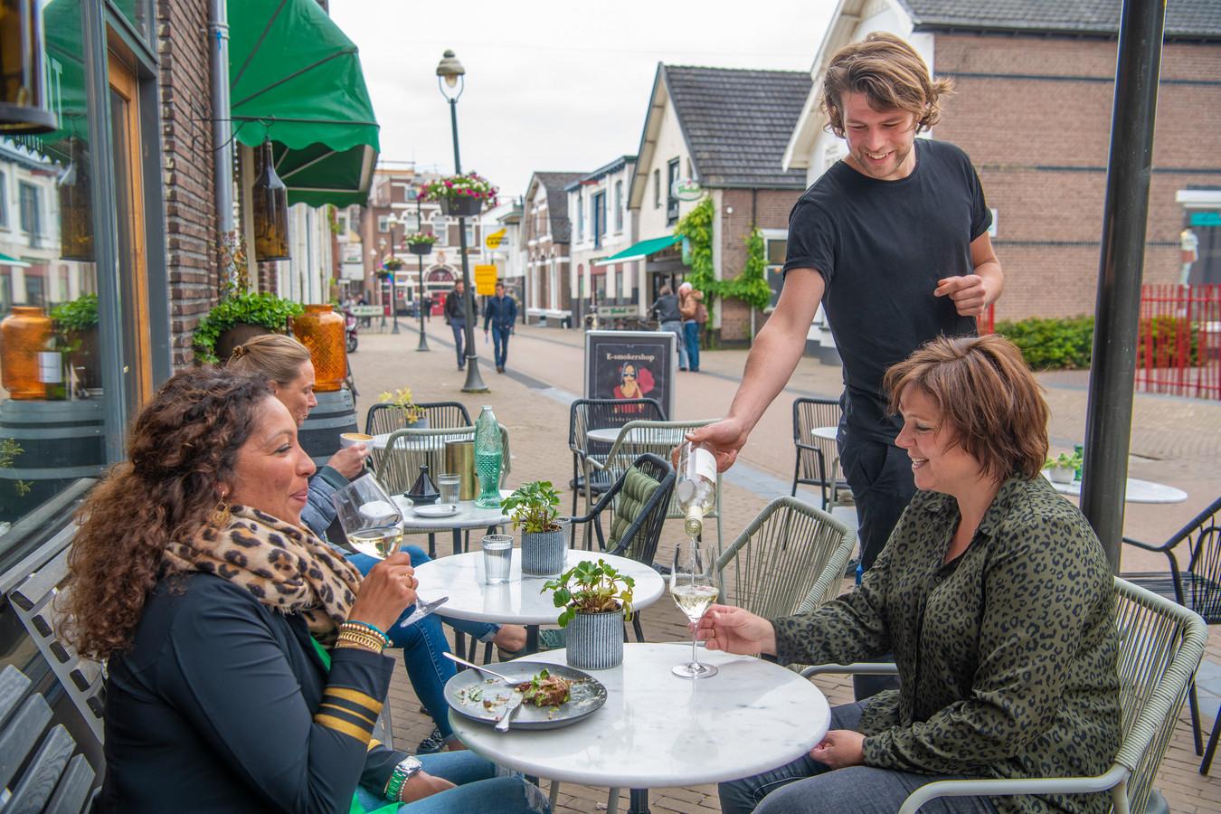 Aaron Post, eigenaar van Lunch- en Wijnbar Rembrandt bedient zijn gasten op het terras aan de Marktstraat.  Hij hoopt net als Café de Flierefluiter - aan de overzijde verderop in de straat, met groene zonwering -  klanten op het terras ook na 23.00 uur een glas wijn in te kunnen schenken.